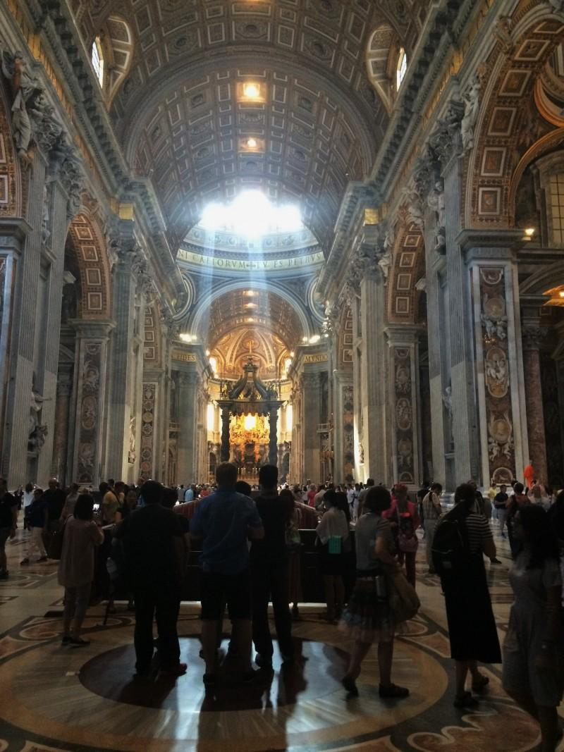 A view of the inside St. Peter's Basilica with Bernini's baldachin illuminated by light coming in through the dome. Three cardinals were there giving mass and the smell of incense filled the massive basilica.  (Marcus Cirone / The DePaulia)