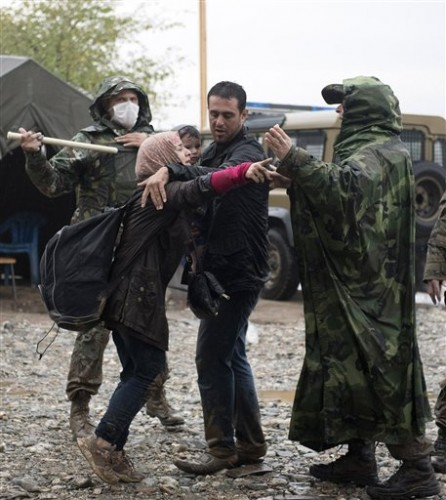 A woman reacts as a Macedonian border policeman try to calm her in the northern Greek village of Idomeni, Thursday, Sept. 10, 2015. Thousands of people, including many families with young children, braved torrential downpours to cross Greece's northern border with Macedonia early Thursday, after Greek authorities managed to register about 17,000 people on the island of Lesbos in the space of a few days, allowing them to continue their journey north into Europe. (AP Photo/Giannis Papanikos)