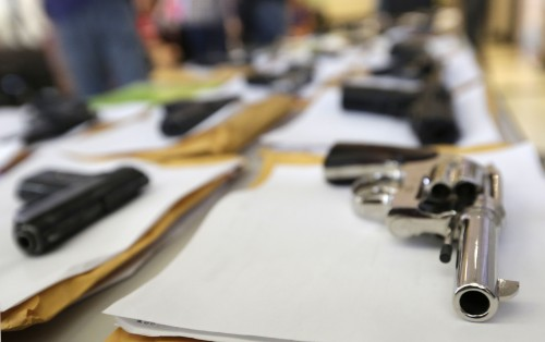 FILE - In this Monday, July 7, 2014, file photo, Chicago police display some of the thousands of illegal firearms they have confiscated so far this year in their battle against gun violence in Chicago. The recent mass shooting at an Oregon community college has put the debate over gun violence and gun control into the center of the presidential race. At least some of the Republicans who are running have pointed to Chicago as proof that gun control laws don't work. (AP Photo/M. Spencer Green)