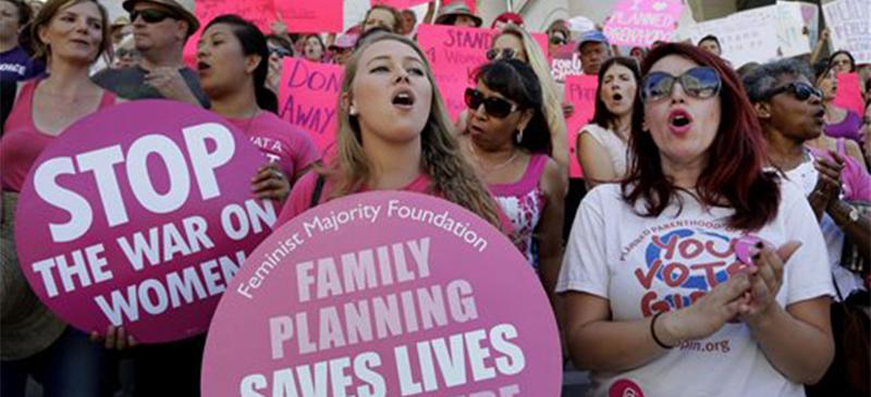 Planned Parenthood supporters rally for women's access to reproductive health care on ``National Pink Out Day'' at Los Angeles City Hall, Tuesday, Sept. 29, 2015. (AP Photo/Nick Ut)