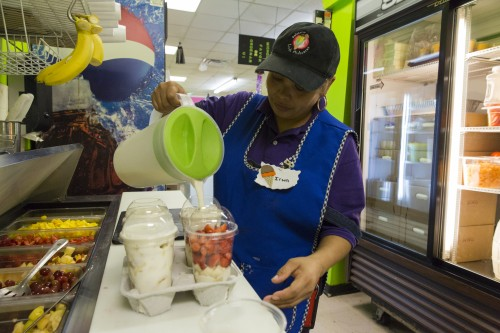 Irma Flores prepares yogur con fruta, made up of extra thick yogurt, strawberries, bananas, mangoes and grapes at La Michoacana. (Photo by Geoff Stellfox | The DePaulia.)