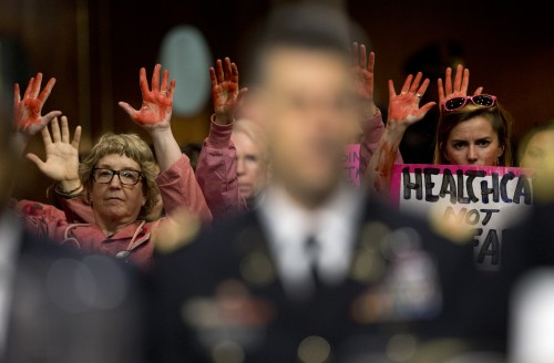 Code Pink members protest the U.S. airstrike on a hospital in Kunduz, Afghanistan behind Gen. John Campbell during the Senate Armed Services Committee hearing Oct. 6, 2015. (Photo courtesy of Carolyn Kaster | AP Photo)