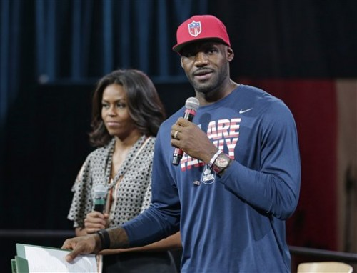 First lady Michelle Obama listens as Cleveland Cavaliers' basketball player LeBron James speaks to parents and children at The University of Akron, Wednesday, Oct. 21, 2015, in Akron, Ohio. James teamed up with Mrs. Obama to celebrate the importance of secondary education at a private event at the University of Akron. The NBA superstar, who went from high school to the pros, and first lady are hosting thousands of children and their parents at the school. (AP Photo/Tony Dejak)