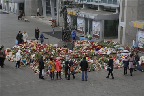 People stand near to floral tributes for the victims of a plane crash, at an entrance of Pulkovo airport outside St. Petersburg, Russia on Wednesday, Nov. 4, 2015. A Russian official says families have identified the bodies of 33 victims killed in Saturday's plane crash over Egypt. The Russian jet crashed over the Sinai Peninsula early Saturday, killing all 224 people on board. Most of them were holidaymakers from Russia's St. Petersburg. (AP Photo/Dmitry Lovetsky)