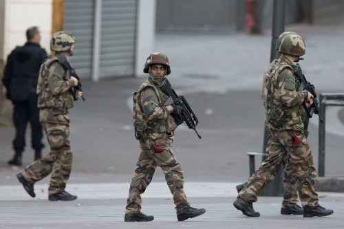 French soldiers patrol during a raid in Saint-Denis, near Paris, Wednesday, Nov. 18, 2015. A woman wearing an explosive suicide vest blew herself up Wednesday as heavily armed police tried to storm a suburban Paris apartment where the suspected mastermind of last week's attacks was believed to be holed up, police said. (Photo courtesy of PETER DEJONG |Associated Press)