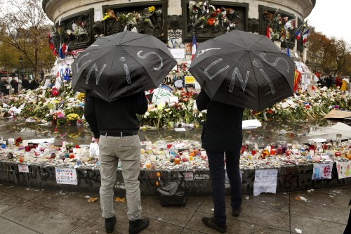 """Two men hold umbrellas that say """"unite"""" while visiting a memorial site in Paris on Thursday, Nov. 19, 2015. (Carolyn Cole/Los Angeles Times/TNS)"""