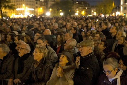 People gather outside for a national service for the victims of the terror attack at Notre Dame cathedral in Paris, Sunday, Nov. 15, 2015. Thousands of French troops deployed around Paris on Sunday and tourist sites stood shuttered in one of the most visited cities on Earth while investigators questioned the relatives of a suspected suicide bomber involved in the country's deadliest violence since World War II. (AP Photo/Daniel Ochoa de Olza)