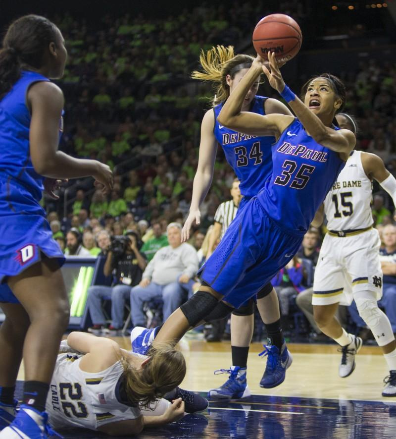 DePaul's Mart'e Grays (35) takes a shot as she trips over Notre Dame's Madison Cable (22) during the second half of an NCAA college basketball game on Wednesday, Dec. 9, 2015, in South Bend, Ind.  (AP Photo/Robert Franklin)