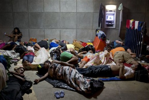 FILE - In this Nov. 21, 2015 file photo, a Cuban woman migrant uses her cell phone while other Cubans sleep, outside of the border control building in Penas Blancas, Costa Rica, on the border with Nicaragua which closed its borders to Cuban migrants. The Costa Rican Foreign Ministry said in a Dec. 28 statement that the first humanitarian transfer will airlift the Cuban migrants from that country to El Salvador in January. From there they will continue by bus toward Mexico. The number of Cubans stranded in Costa Rica has reached at least 8,000 since neighboring Nicaragua closed its border to them weeks ago.  (AP Photo/Esteban Felix, File)