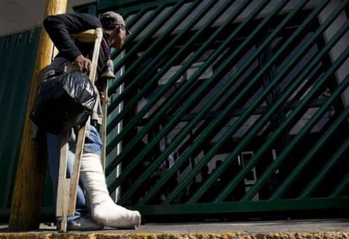 "Wilmer Antonio Almendari a migrant from Honduras who broke his leg while riding the train through Mexico toward the U.S. border, waits outside the Agujas immigration detention center, in Mexico City, Tuesday, Jan. 5, 2016. Almendari says that he was riding the train known as ""La Bestia"" or ""The Beast"" as it rolled into Mexico City and was mugged and thrown off the the train. He broke his leg in the fall and was treated at a local hospital. He turned himself in, to Mexican immigration authorities and was asking for help to return back to his home country, Honduras. (AP Photo/Marco Ugarte)"