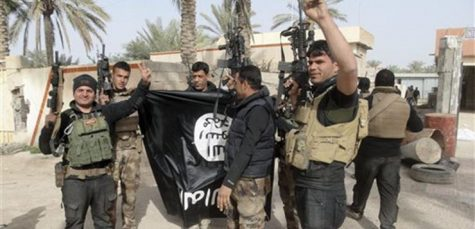 In this Tuesday, Jan. 19, 2016 photo, Iraqi security forces celebrate as they hold a flag of the Islamic State group they captured in Ramadi, 70 miles (115 kilometers) west of Baghdad, Iraq. The Islamic State group, which controls large parts of Syria and Iraq where it declared an Islamic caliphate in June 2014, suffered several defeats recently in both countries, including the loss of the Iraqi city of Ramadi and parts of northern and northeastern Syria over the past months. (AP Photo)