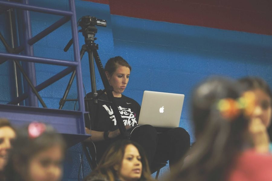 Katherine Harry held the DePaul record for most games played during her tenure. Harry sits in the top row of the bleachers during the game with her laptop. (Photo by Olivia Jepson | The DePaulia)