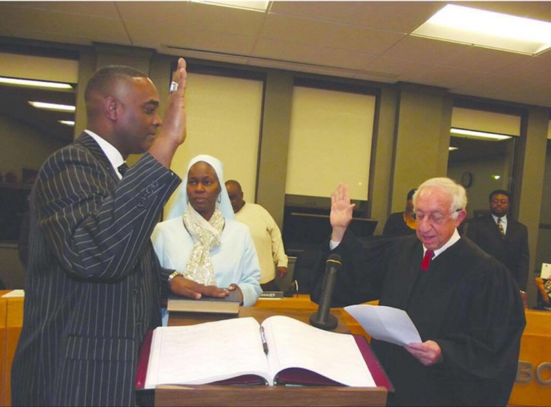Marcus Muhammad, left, stands with his wife Abisayo as he is sworn in by former Chief Justice of Berrien County Judge Alfred Butzbaugh Dec. 23. (Photo courtesy of SAM HOWZIT)