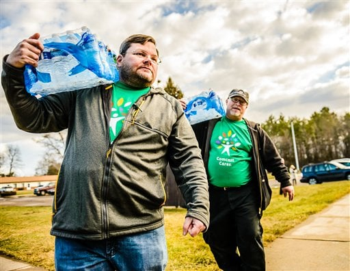Michigan Representative Phil Phelps (D-Flushing), left, and Comcast employee Lloyd Richards deliver cases of water to residents at Slidell Senior Housing Saturday, Feb. 20, 2016 in Flint, Mich. (Kevin W. Fowler/AP Images for Comcast)