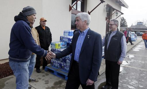 In a file photo from Feb. 5, 2016, Michigan Gov. Rick Snyder, center and Our Lady of Guadalupe Church Deacon Omar Odette, right, meet with volunteers helping to load vehicles with bottled water in Flint, Mich. Snyder's standing as one of the GOP's most accomplished governors has taken a beating in the lead-contaminated water emergency in Flint. Democrats, especially those running for president, are pointing to mistakes by Snyder's administration during the crisis as a vivid example of Republican-style cost-cutting run amok. (AP Photo/Carlos Osorio)