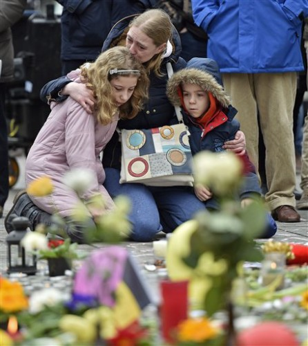 People mourn for the victims of the bombings at the Place de la Bourse in the center of Brussels, Wednesday, March 23, 2016. Bombs exploded yesterday at the Brussels airport and one of the city's metro stations Tuesday, killing and wounding scores of people, as a European capital was again locked down amid heightened security threats. (AP Photo/Martin Meissner)