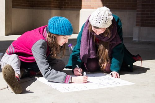 Sophomore political science student Madeline Mosso (right) and sophomore elementary education student Helen Kinskey draw a sign before heading downtown to protest in solidarity with the Chicago Teacher's Union. (Kirsten Onsgard / The DePaulia)