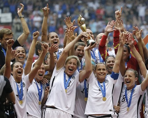 FILE - In this July 5, 2015, file photo, the United States Women's National Team celebrates with the trophy after they beat Japan 5-2 in the FIFA Women's World Cup soccer championship in Vancouver, British Columbia, Canada. Five players from the World Cup-winning U.S. national team have accused the U.S. Soccer Federation of wage discrimination in an action filed with the Equal Employment Opportunity Commission. Alex Morgan, Carli Lloyd, Megan Rapinoe, Becky Sauerbrunn and Hope Solo maintain in the EEOC filing they were paid nearly four times less than their male counterparts on the U.S. men's national team. The filing was announced Thursday in a statement from the law firm representing the players.  (AP Photo/Elaine Thompson, File)