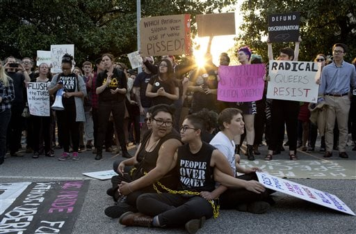 Front from left, demonstrators Jess Jude, Loan Tran and Noah Rubin-Blose sit chained together in the middle of the street during a protest against House Bill 2 Thursday, March 24, 2016, outside of the Governor's Mansion on North Blount Street in downtown Raleigh, N.C. (Jill Knight/The News & Observer via AP)