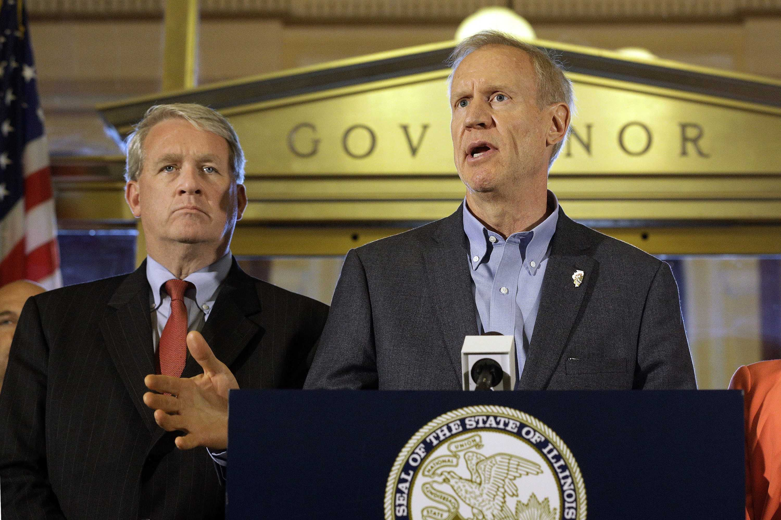 Illinois Gov. Bruce Rauner speaks to reporters in front of his office at the Illinois State Capitol June 30 in Springfield, Illinois. Lawmakers were moved to compromise on a stopgap budget after a year-and-a-half stalemate by a powerful force: a high-stakes November election and a voting public one legislator described as near revolt. Rauner signed legislation Thursday evening to keep state government operating for six months and schools open for another year. The plan allows the politicians to campaign without the threat of shuttered schools. Looking on is Illinois House Minority Leader Jim Durkin, R-Western Springs. (AP Photo/Seth Perlman)