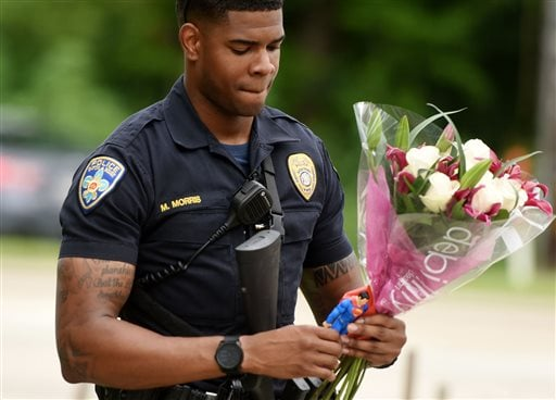 Baton Rouge Police Department Officer Markell Morris holds a bouquet of flowers and a Superman action figure that a citizen left at the Our Lady of the Lake Hospital where the police officers were brought this morning, Sunday, July 17, 2016. Multiple law enforcement officers were killed and wounded Sunday morning in a shooting near a gas station in Baton Rouge. (Henrietta Wildsmith |The Times via AP)