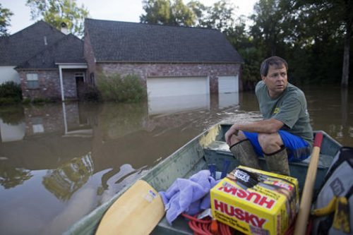 David Key boats away from his flooded home after reviewing the damage in Prairieville, La., Tuesday, Aug. 16, 2016. Key, an insurance adjuster, fled his home as the flood water was rising with his wife and three children and returned today to assess the damage. (Max Becherer | AP Photo)