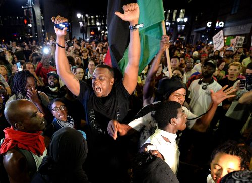 Protesters celebrate their arrival at Trade and College Streets in Charlotte, N.C., on Thursday, Sept. 22, 2016, as demonstrations continue following the shooting death of Keith Scott by police earlier in the week. (Jeff Siner/Charlotte Observer/TNS)