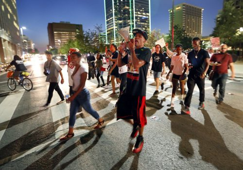 Protesters cross Commerce Street during the Next Generation Action Network protest in downtown Dallas, Thursday, Sept. 22, 2016. Dominique Alexander the leader of the Dallas group behind a July march at which five police officers were killed by a sniper has led a downtown Dallas protest rally the day he left prison. He led a rally Thursday night to protest the fatal police shooting of black men in Tulsa, Okla., and Charlotte, N.C. (Tom Fox/The Dallas Morning News via AP)
