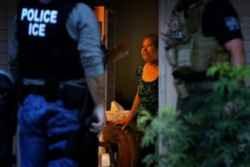 ICE Enforcement and Removal Operations officers, in search of 32-year-old Hugo Medina, question his mother Magdalena Medina, 69, about his whereabout in a morning raid on his residence on Aug. 12, 2015 in Riverside, Calif. (Irfan Khan/Los Angeles Times/TNS)