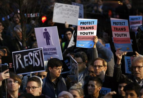 Protesters hold signs at a rally in support of transgender youth, Thursday, Feb. 23, 2017, at the Stonewall National Monument in New York. They were demonstrating against President Donald Trump's decision to roll back a federal rule saying public schools had to allow transgender students to use the bathrooms and locker rooms of their chosen gender identity. The rule had already been blocked from enforcement, but transgender advocates view the Trump administration action as a step back for transgender rights. (AP Photo/Kathy Willens)
