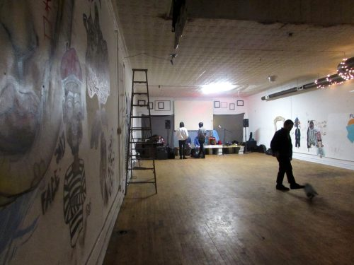 Artists walk the empty apartment as others set their speakers and equipment up before guests arrive at the D.I.Y. music venue for the concert. (Molly O'Mera / The DePaulia)