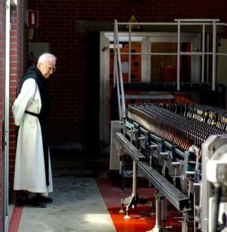 A Trappist monastery employee examines the bottling line at the Rochefort Brewery in Rochefort, Belgium.  (Photo Courtesy of Shiffer Publishing, LTD)