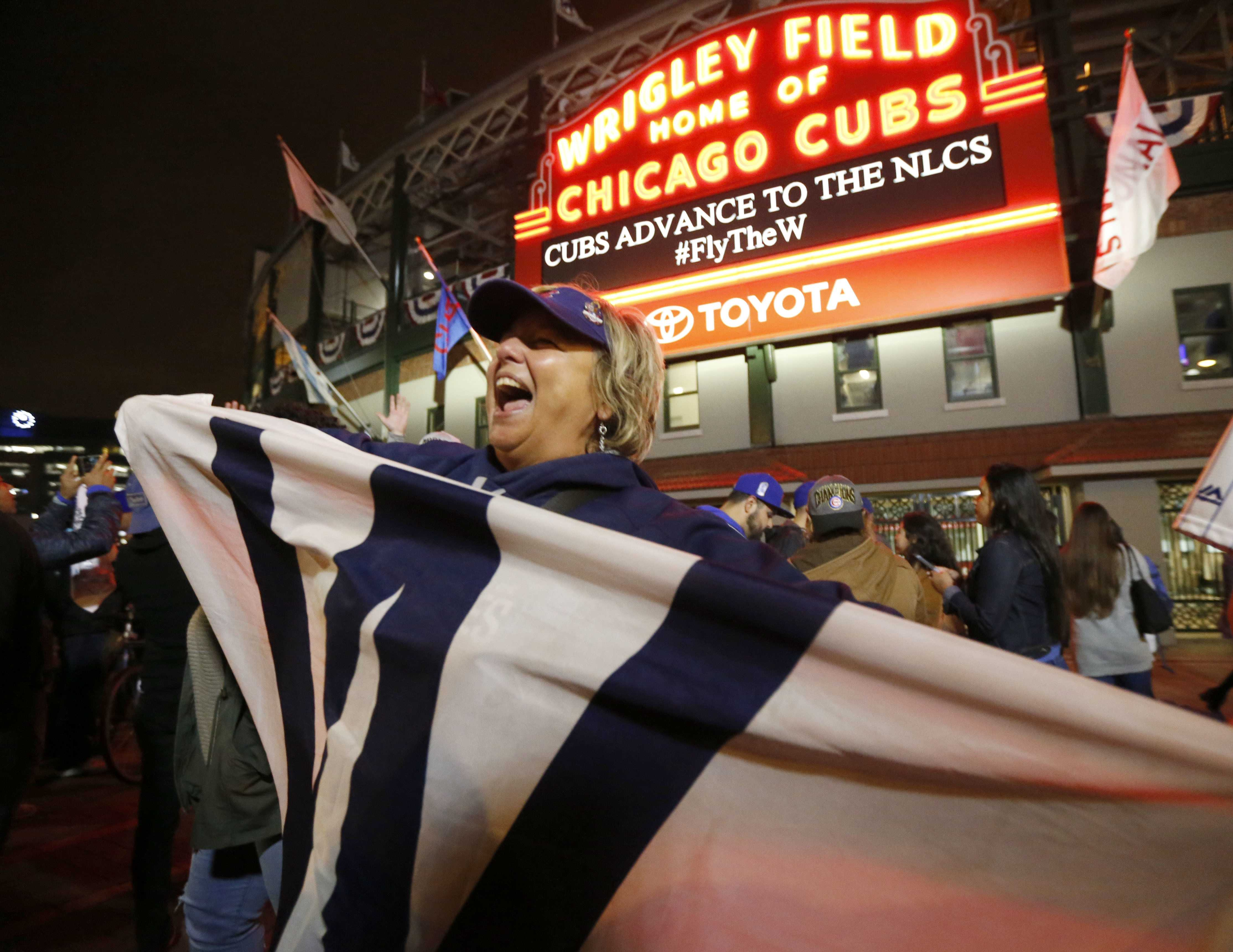 Chicago Cubs fans celebrate outside Wrigley Field on Thursday, Oct. 12, 2017, in Chicago, after the Cubs defeated the Washington Nationals 9-8.  (Charles Rex Arbogast/The Associated Press)