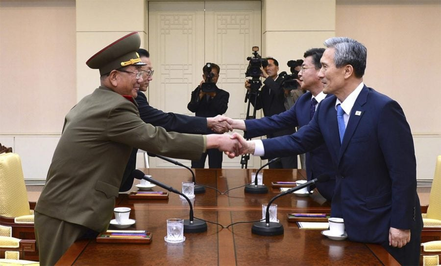 In this Aug. 22, 2015 file photo South Korean National Security Director, Kim Kwan-jin, right, and Unification Minister Hong Yong-pyo shake hands with Hwang Pyong So, left, and Kim Yang Gon during their meeting at the border village of Panmunjom in Paju, South Korea.