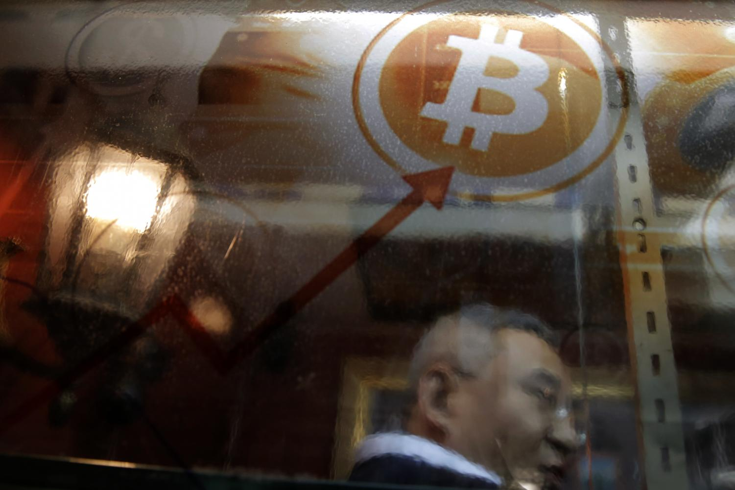 In this Friday, Dec. 8, 2017, file photo, a man uses a Bitcoin ATM in Hong Kong. Kin Cheung | AP