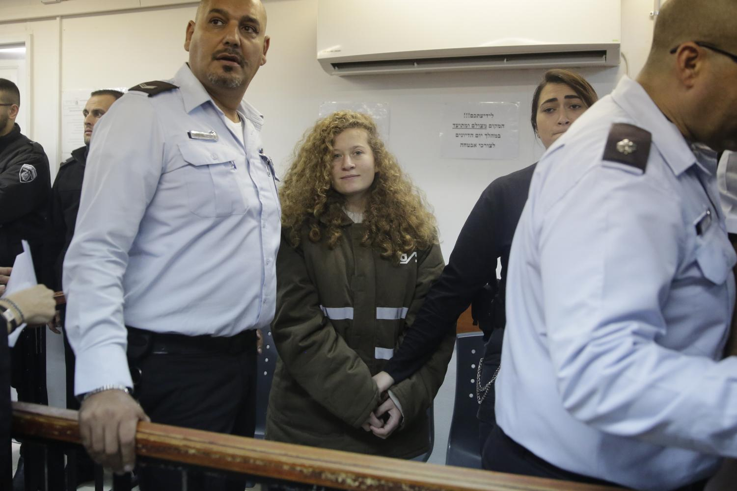 Ahed Tamimi is brought to a courtroom inside the Ofer military prison near Jerusalem, Monday, Jan. 15, 2018. Tamimi, 16, was filmed in December pushing, kicking and slapping Israeli soldiers, who stood by silently.  (Mahmoud Illean | AP)