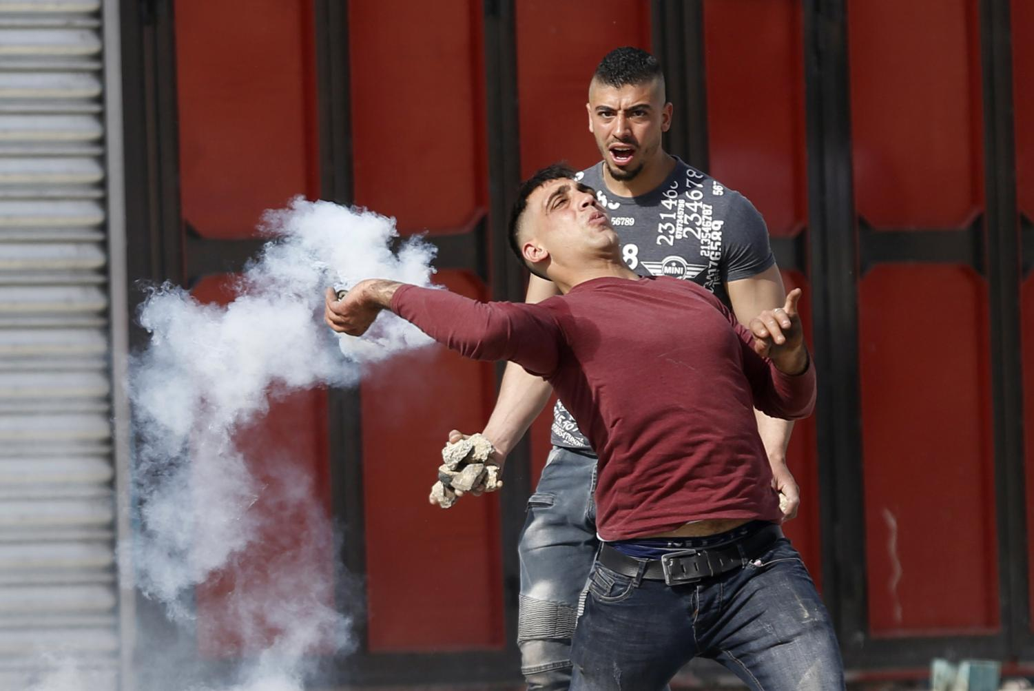 A Palestinian man hurls a tear gas grenade back at Israeli police forces in a clash on the Gaza Strip. (Photo courtesy of the Associated Press)