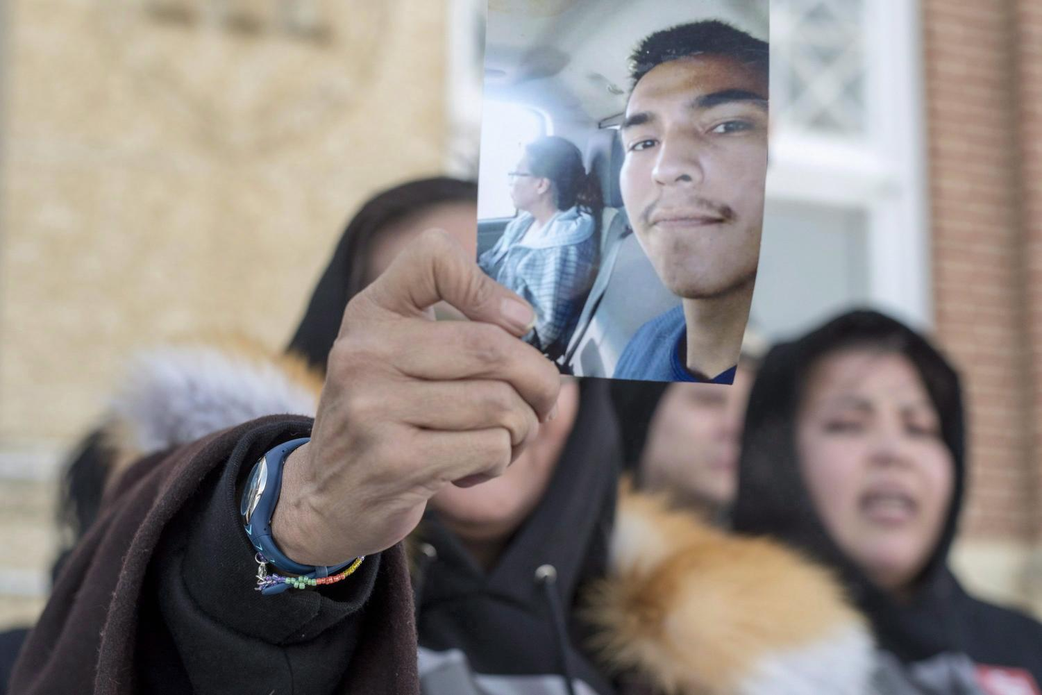 Debbie Baptiste holds up a picture of her son, Colten Boushies on the fifth day of the trial of Gerald Stanley, the farmer accused of killing the 22-year-old Indigenous man, in Battleford, Saskatchewan on Feb. 5, 2018. (Liam Richards | The Canadian Press via AP)