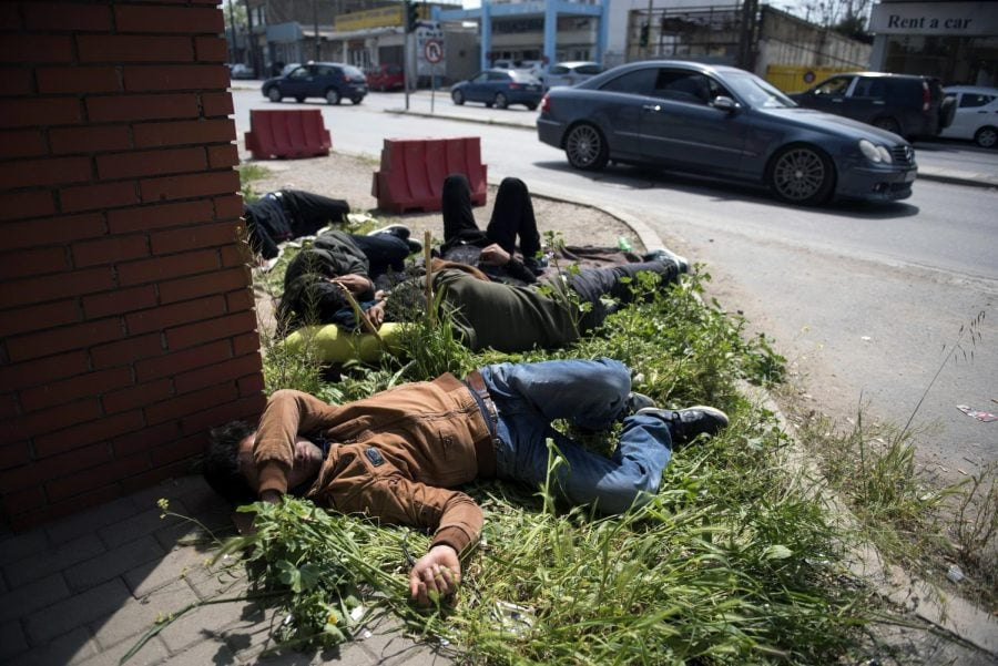 Migrants sleep outside the police headquarters at the northern Greek city of Thessaloniki, Friday, April 13, 2018. Several hundred refugees and migrants have gathered outside a police station in Greece's second largest city, waiting for hours to be formally arrested and gain temporary residence in the European Union country.