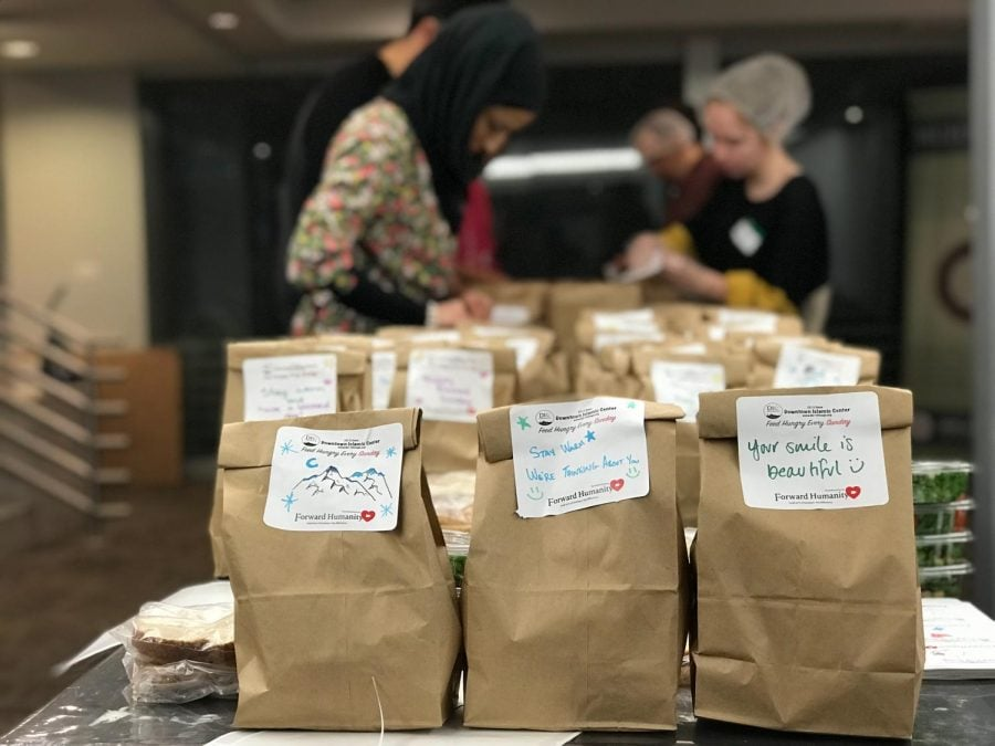 Forward Humanity volunteers prepare bags of food in the basement of the  Downtown Islamic Center (DIC), that contain a banana, water, peanut butter  sandwich and salad. They put inspirational stickers on them before distributing to homeless people in the Chicago Loop.  (Yousef Alamer | The DePaulia)