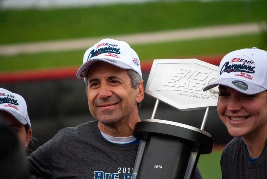 Head Coach Eugene Lenti holds the Big Easr Conference title trophy.
