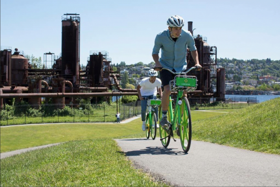 People riding LimeBikes past a rusted plant in Seattle, Washington. Seattle is one of many cities in U.S. who adopted dockless bike sharing.
