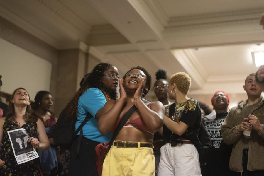 Amidst the heat in City Hall, demonstrators sing and dance for proper funding in their communities.