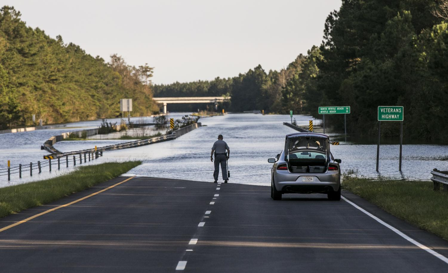 S.C. Highway 22 is flooded between SC-90 and SC-905 on Saturday, Sept. 22, 2018, in Conway, S.C. An officer with the South Carolina State Highway Patrol marks the water level to compare against previous days. The blocked road has traffic snarled around Conway and the Waccamaw River continues to rise past record levels.