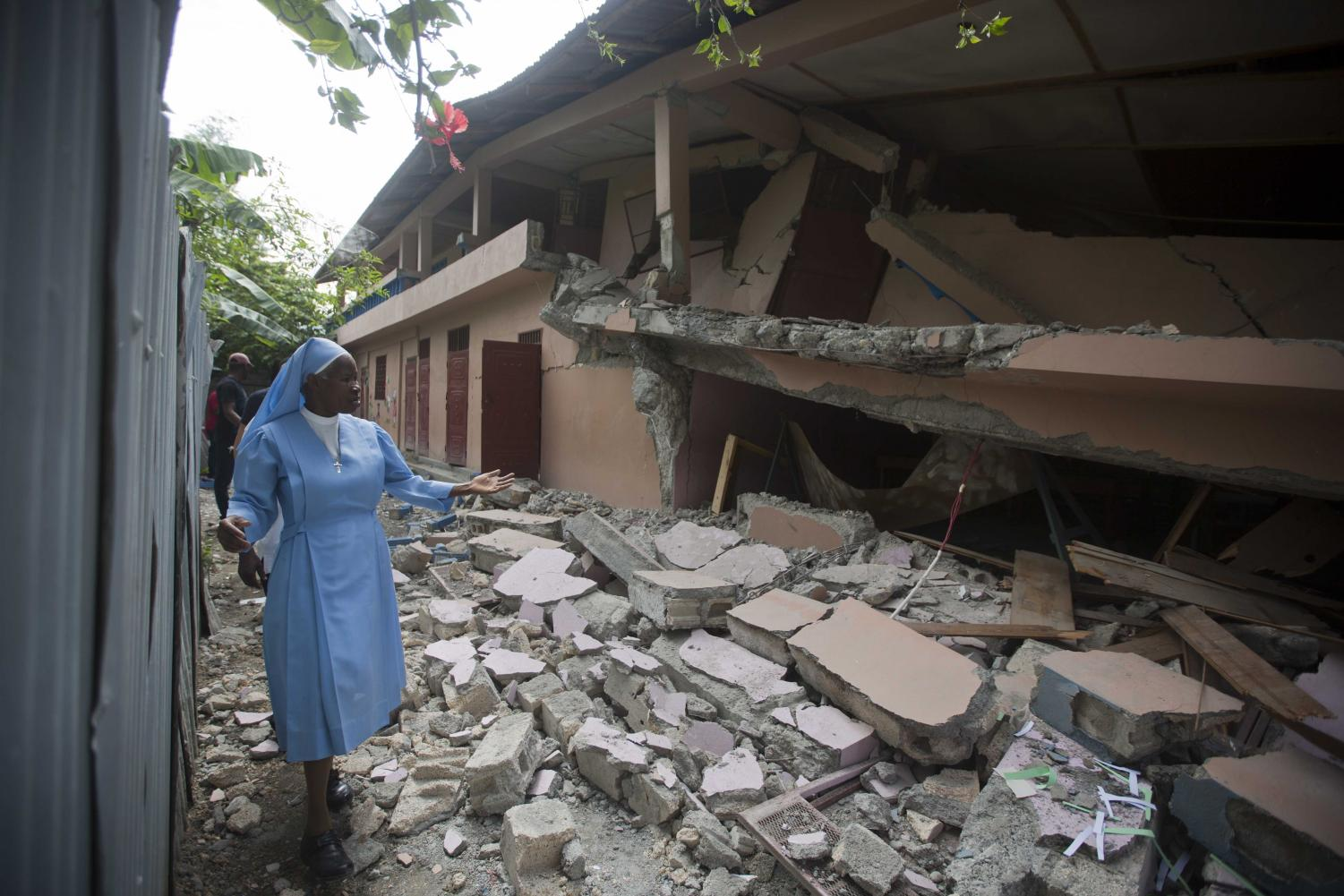Sr Maryse Alsaint walks alongside a school damaged by a magnitude 5.9 earthquake the night before, in Gros Morne, Haiti, Sunday, Oct. 7, 2018. Emergency teams worked to provide relief in Haiti on Sunday after the quake killed at least 11 people and left dozens injured.