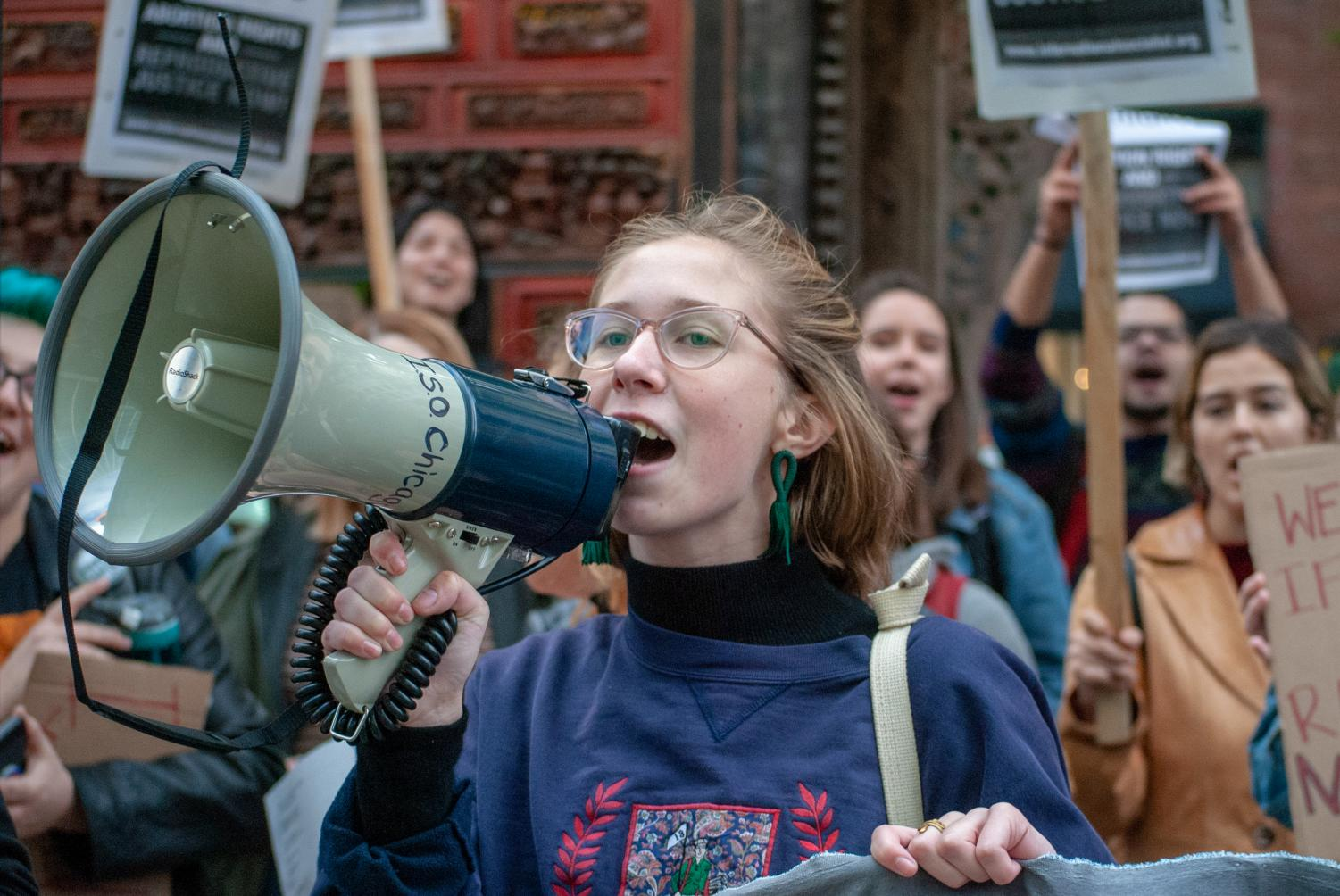Holding onto a megaphone, a protester stands outside the American Bar Association Chicago in opposition of the nomination of Judge Brett Kavanaugh following sexual assault claims.