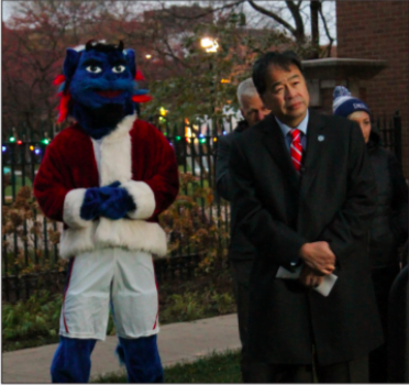 Dibs (left) stands with DePaul president Gabriel Esteban (right) during the tree lighting ceremony in Lincoln Park on Wednesday.