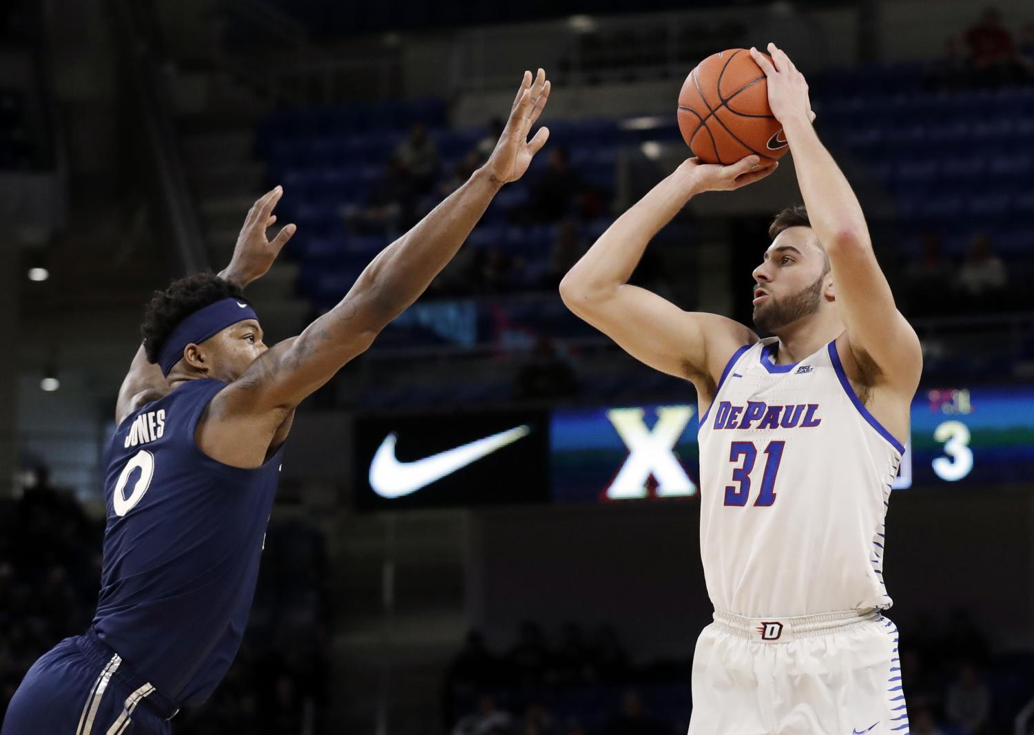 DePaul forward Max Strus, right, shoots against Xavier forward Tyrique Jones during the second half of an NCAA college basketball game Saturday, Dec. 29, 2018, in Chicago. Xavier won 74-65. Nam Y. Huh | AP