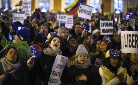 In this Wednesday, Jan. 23, 2019  le photo, people gather during a protest against Venezuela's Nicolas Maduro and in support of an opposition leader self-proclaimed as the interim president of the country in Madrid, Spain.