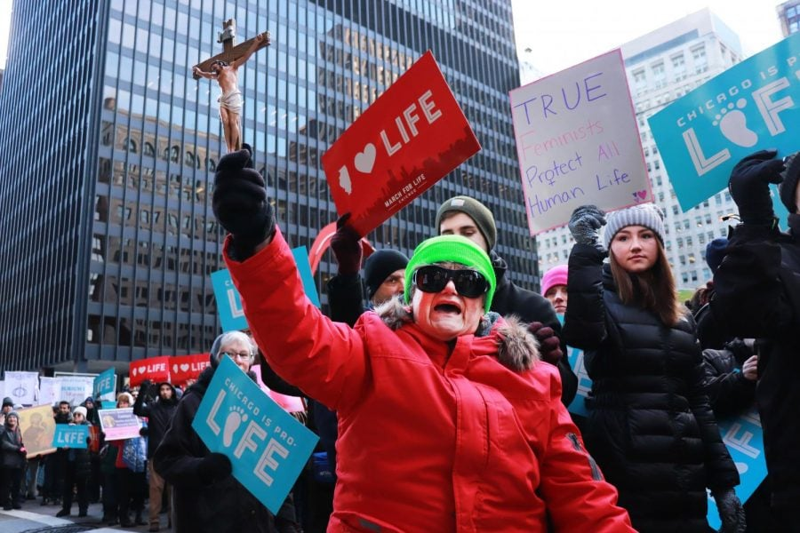 With a cross in one hand, a woman joins alongside fellow protestors during the March for Life in an effort to make abortions illegal.